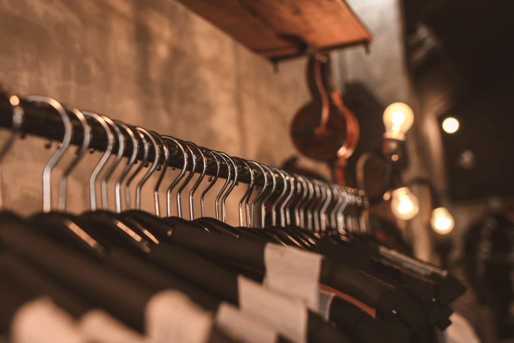 tailored training 121 coaching page photo of lightbulbs above clothes on black hangers