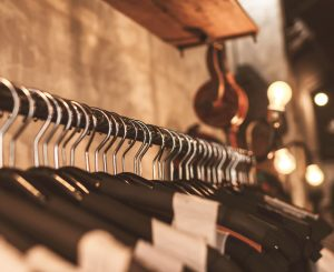 Retail business 121 coaching training photo of lightbulbs above clothes on black hangers